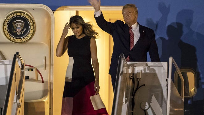 President Donald Trump waves to supporters with First Lady Melania Trump as they arrive at Palm Beach International Airport in West Palm Beach, Friday, Feb. 14, 2020.