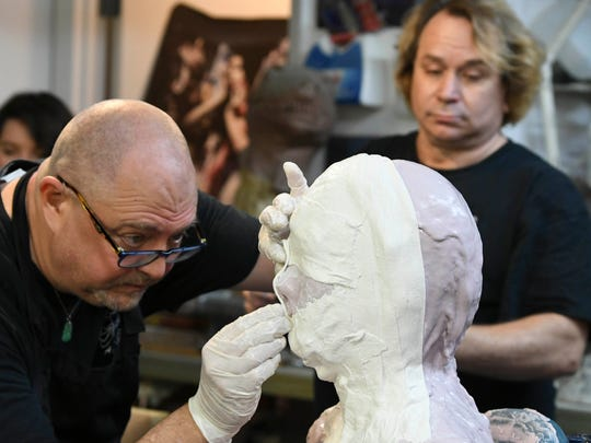 Ashley Green and Alan Ostrander and Ray Asiala of AEO Studios apply gauze over the casting material on Christina's head.