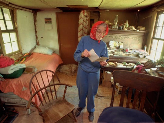 "Inside the simple cabin she has lived in since 1916, Birdle Manon looks up a name in her church directory on Dec. 5, 1997. ""I don't get lonesome - I'm not a person who gets lonesome,"" she says, ""I've never been lonely in my life."""