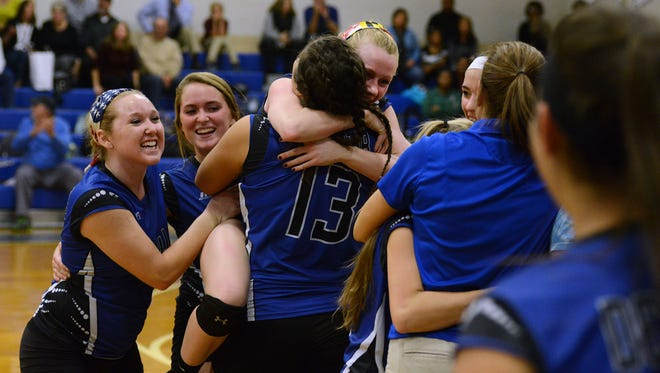 Members of the Stephen Decatur volleyball team celebrate their victory over Bennett Monday night in Berlin.