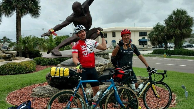Paul Bedard, left, and John Correiro posed for this iconic statue of surfer Kelly Slater in Cocoa Beach, Fla. on the first day of their Florida-to-Massachusetts bicycle ride last month.