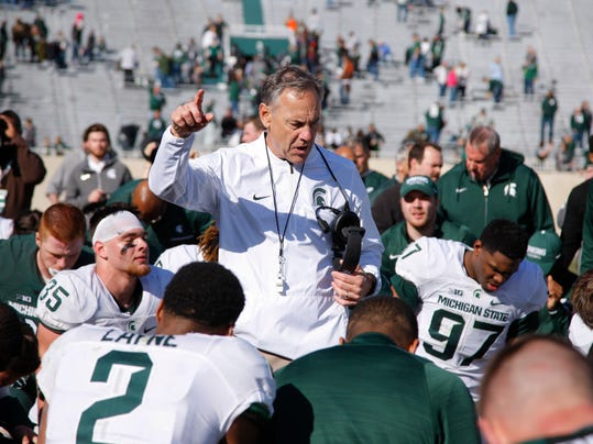 Michigan State coach Mark Dantonio, center, talks to his players following a spring NCAA college football scrimmage, Saturday, April 1, 2017, in East Lansing, Mich. The defense won 33-23. (AP Photo/Al Goldis)
