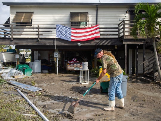 Harvey Pennell works to shovel a thick layer of mud from the driveway of his home in Plantation Island, an unincorporated area near Everglades City, as Collier County began picking up the pieces in the aftermath of Hurricane Irma on Tuesday, Sept. 12, 2017.