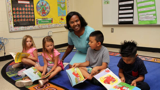 Kindergarten teacher Kathy Hudson reads with students Zoey and Reagan Hardy, Angel Corona and David Romero Hernandez at the Back to School Orientation event at Oaks Road Academy in New Bern, N.C., August 22, 2019. Teachers and staff talk with students and parents about the school, classroom information, bus assignments and  learning materials.