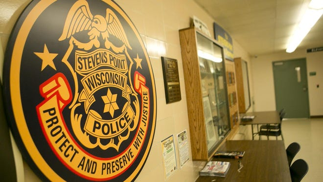 The Stevens Point Police Department logo hangs in the lobby of the police department in the basement of County-City Building.
