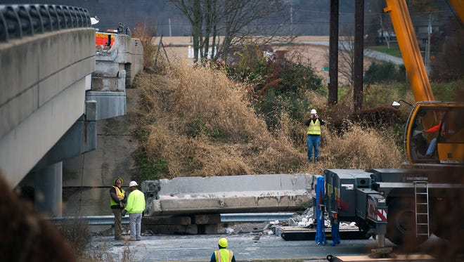 Crews work on a Route 30 overpass that was damaged Monday night. The closed eastbound lanes were expected to reopen Wednesday night.