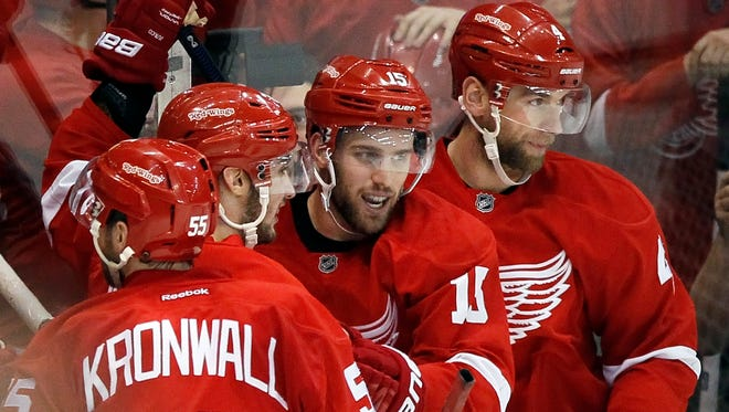 Detroit Red Wings' Riley Sheahan (15) celebrates with Niklas Kronwall (55), of Sweden, Tomas Jurco, of Slovakia, and Jakub Kindl, right, of the Czech Republic  after scoring a goal against the New Jersey Devils during the third period of an NHL hockey game at Joe Louis Arena Tuesday, Dec. 22, 2015, in Detroit.