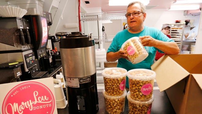 Owner Jeff Waldon unpacks flavored popcorn Wednesday, May 30, 2018, at Mary Lou Donuts, 1830 S. Fourth Street in Lafayette. Mary Lou Donuts is now serving its own line coffees and snack foods including a variety of popcorn flavors, pretzels covered with dark chocolate, milk chocolate, white chocolate and peanut butter, even chocolate covered potato chips.