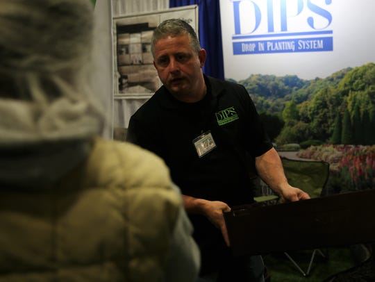 """Scott Meyer, of Wallkill, shows off his """"Drop In Planting System,"""" or """"DIPS,"""" which is a series of interconnected containers that holds seeds and dirt and goes into the ground. He said the company began about two months ago."""