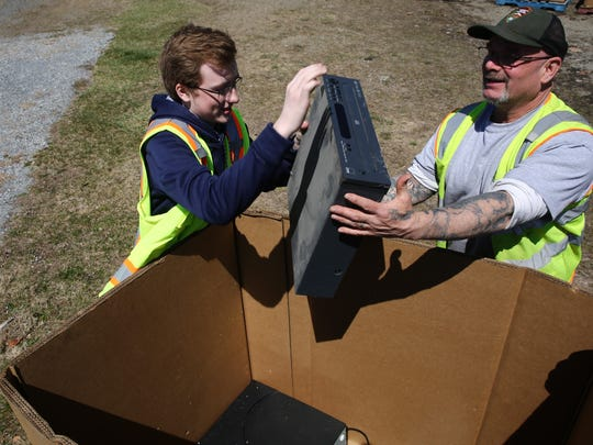 FDR High School student Owen Riegle, left, and National Parks Service employee John Misch load an electronic item into a box on Saturday. The recycling event was held in recognition of Earth Day.
