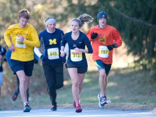 Runners take part in the Turkey Trot 5-mile race at Arlington High School on Thursday.