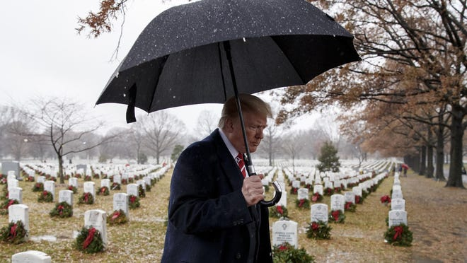 President Donald Trump walks with an umbrella from Section 60 of Arlington National Cemetery in Arlington, Va., Saturday, Dec. 15, 2018, after visiting during Wreaths Across America Day. Wreaths Across America was started in 1992 at Arlington National Cemetery by Maine businessman Morrill Worcester and has expanded to hundreds of veterans' cemeteries and other locations in all 50 states and beyond.