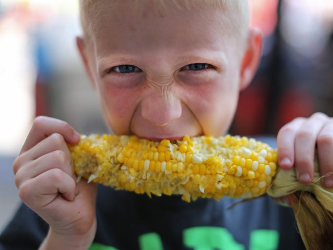 Keagan Leisure, 8, of Mason, enjoys an ear of fresh corn from Pit to Plate at Taste of Cincinnati Saturday. The three day event along Fifth street downtown includes food, drinks, entertainment, rides and other games for kids and much more. Thousands are expected to participate. In addition to taste, the Reds are in town all weekend as well.