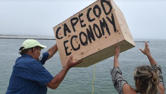 Kevin Richards and his wife, Kathy Gianno, owners of The Loft Restaurant and Bar in West Yarmouth, throw a crate representing Cape Cod's economy from the deck at Smugglers Beach in South Yarmouth.