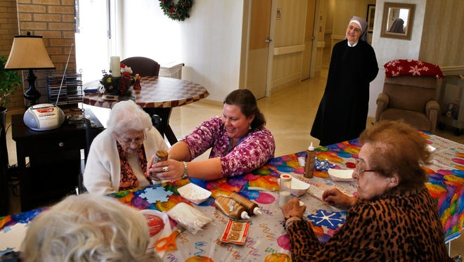 As Mother Patricia Mary watches, volunteer coordinator Lindsey Graveley helps residents with art projects at the elderly home run by Little Sisters of the Poor in Denver.