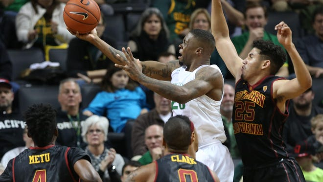 Oregon's Elgin Cook, top center, goes up for two points under pressure from Southern California's Chimezie Metu (4), Darion Clark (0) and Bennie Boatwright, right, during the second half of an NCAA college basketball game Thursday, Jan. 21, 2016 in Eugene, Ore. (AP Photo/Chris Pietsch)