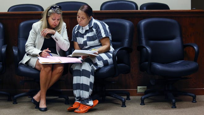 Assistant Public Advocate Melanie Lowe discusses the case with one of her clients at the Oldham County courthouse. Aug. 13, 2015