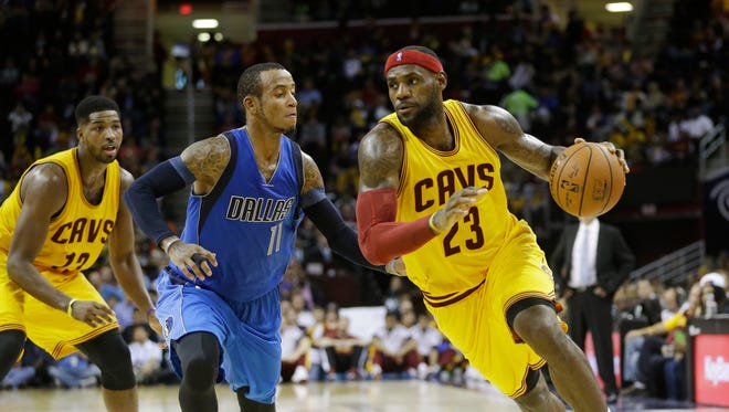 Cleveland Cavaliers' LeBron James (23) drives past Dallas Mavericks' Monta Ellis (11) in preseason Friday. James returned to Cleveland after winning two championships with the Miami Heat.