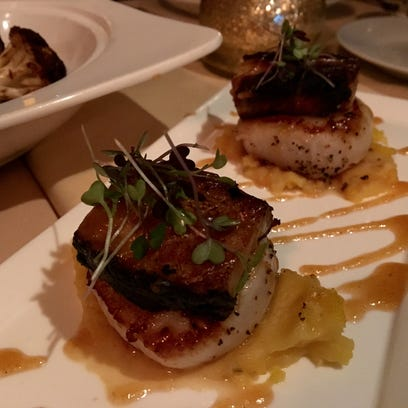 Square of pork belly sit atop plump scallops and a