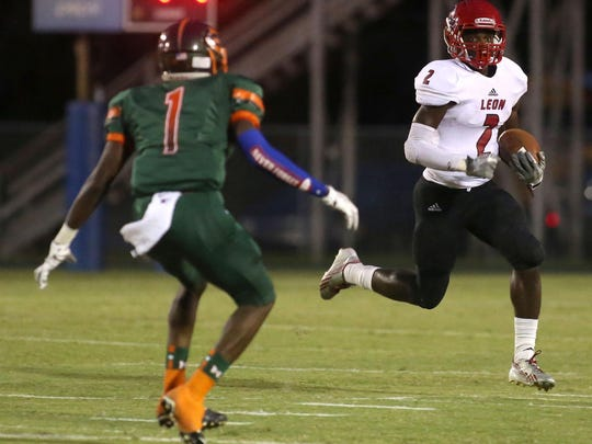 Leon's James Peterson runs the ball past Mosley's Devontia Wilson. Mosley faced off with Leon during a football game on Sept. 10.