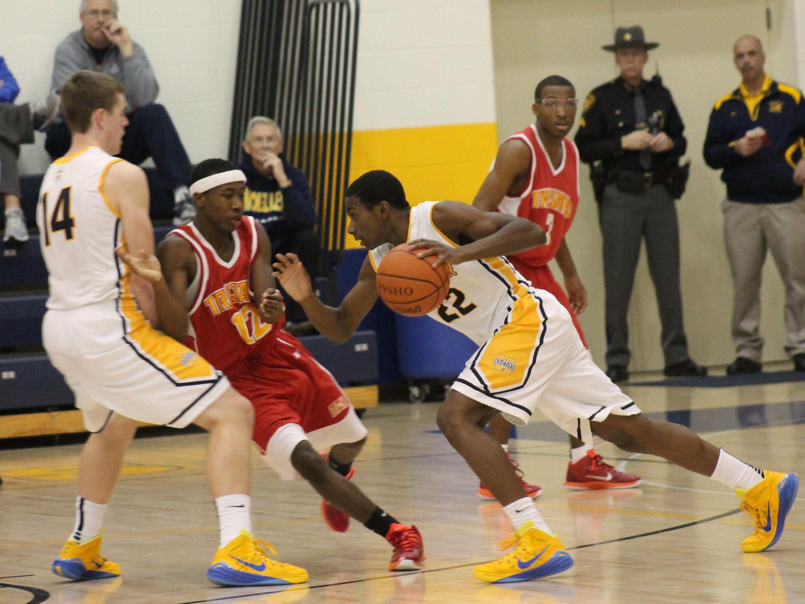 Moeller's Trey McBride prepares to drive around the pick of Riley Voss (14) against North College Hill last season.