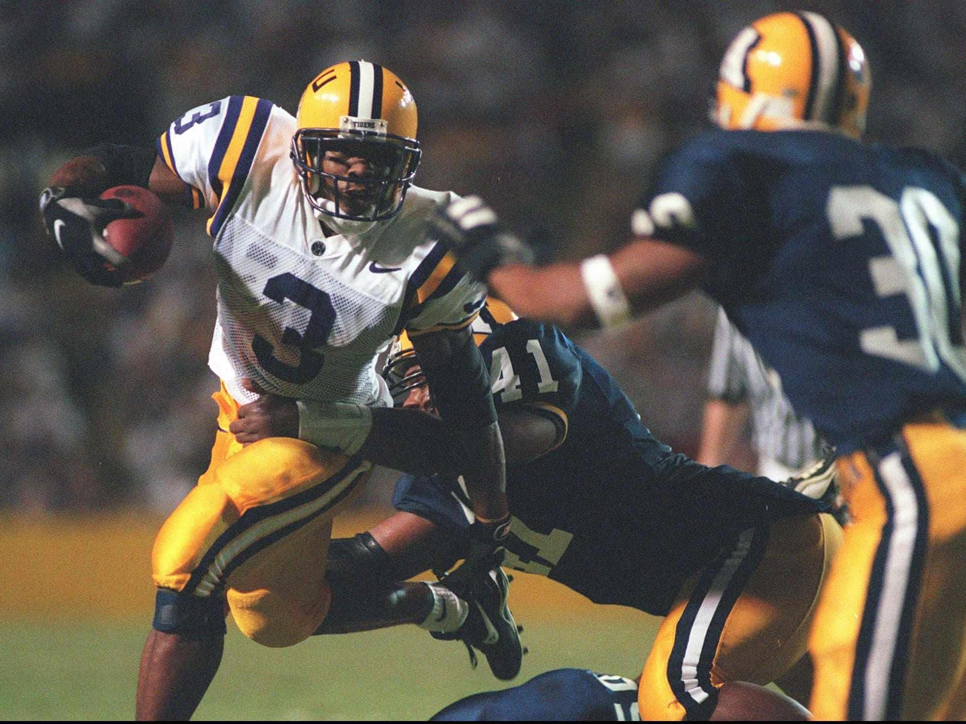 LSU's Kevin Faulk (3) runs for a first down picking up 6 yards before being brought down by Akron's Corey Christian (41) and Rich Reliford (30) a 1997 game in Tiger Stadium.