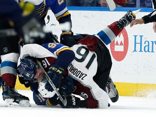 St. Louis Blues' Vladimir Tarasenko (91), of Russia, and Colorado Avalanche's Nikita Zadorov (16), of Russia, fight during the first period of an NHL hockey game Thursday, Feb. 8, 2018, in St. Louis. (AP Photo/Jeff Roberson)