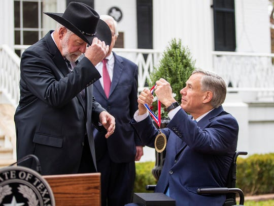 Gov. Greg Abbott presents the Governor's Medal of Courage on Monday to Jack Wilson, who shot and killed a gunman who opened fire on the congregation and killed two people at West Freeway Church of Christ in White Settlement, Texas, on Dec. 29.