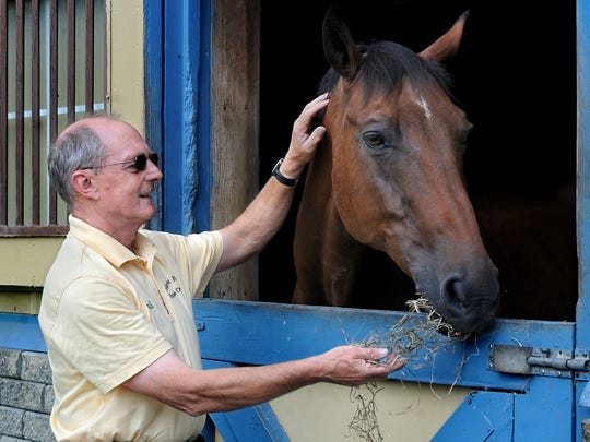 Paul Lindsay, the owner of Cedar Crest Farm Equestrian Center in Pine Plains, gives Jasper, 18, a bay Mecklenburg, a little hay while discussing the horse's 10-year-long battle with chronic Lyme disease.