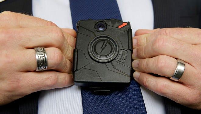 Steve Tuttle, vice president of communications for Taser International, demonstrates one of the company's body cameras.