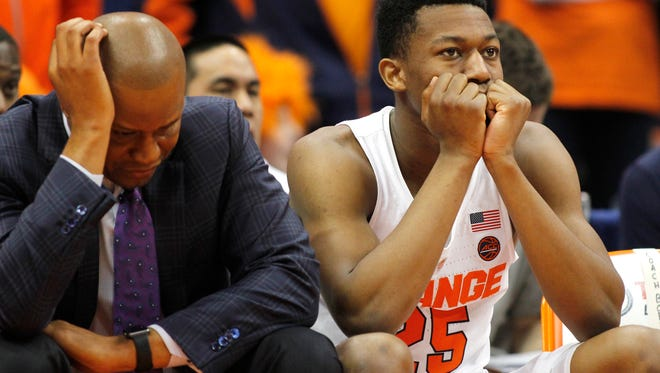 Syracuse assistant coach Adrian Autry, left, and Syracuse's Tyus Battle watch the game from the bench in the final seconds in Syracuse on Monday. Louisville won 76-72.