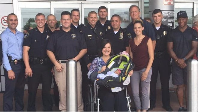 Surrounded by Summit police officers, Victoria Tarentino leaves Overlook Medical Center in Summit with her newborn daughter, Anastasia.