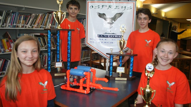The Sanford Ospreys' Emily Sherrier, left, Owen Andreasen, Aaron White and Sofia Vietri with their trophies and winning robot. The team will present their design later this month at the Biennial Intelligent Ship Symposium at the University of Pennsylvania.