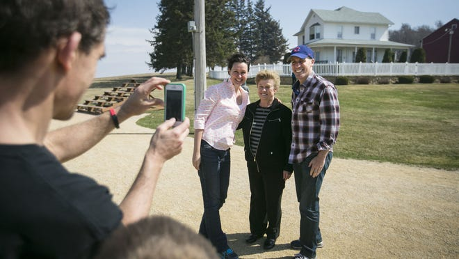 "Eva Penar, 36, left, and Andrew Hillsberg, right, 43, have their picture taken with Betty Boekenstedt, center, at the ""Field of Dreams"" movie site April 12, 2014, near Dyersville, Iowa. Boekenstedt grew up in the farmhouse used in the movie."