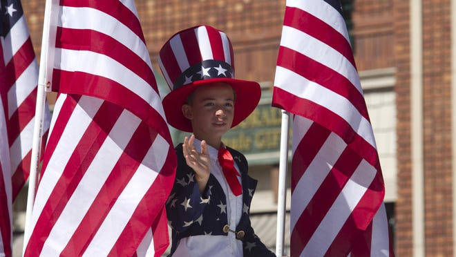 A participant in a Southern Utah Fourth of July parade waves to spectators.