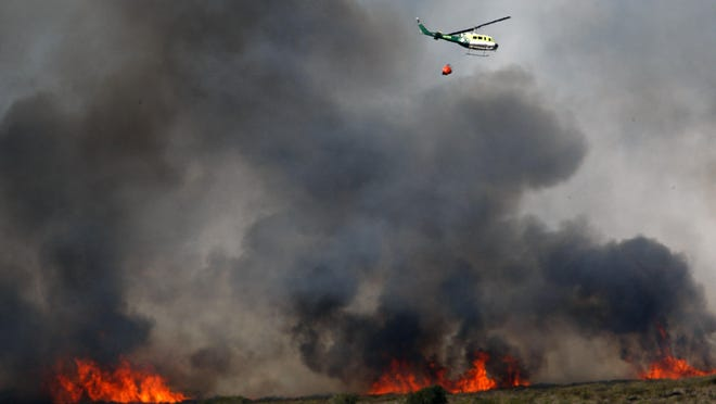 Several helicopters were used to douse the prescribed 220 acre burn Oct. 6, 2009, on the former Fort Ord army base after weather conditions changed. Burning brush helps expose unexploded munitions and explosives left from when Fort Ord was used for military training.