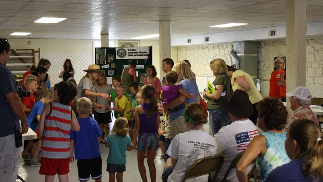 """The Buffalo National River Park Service sent park ranger Pamela DeYoung, center, to create a """"thunderstorm"""" inside the Marion County Fairgrounds Community Building during the recent Environmental Awareness Day hosted by Marion County Library. It only was one of many fun and educational hands-on activities that were offered during the event."""