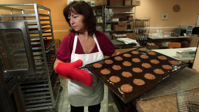 Linda Beg puts in a tray full of Paleo carrot apple muffins at her Starseed Bakery. The market for Starseed's products ranges from people with Celiac disease to people who do CrossFit training to those who just want to eat more healthfully.