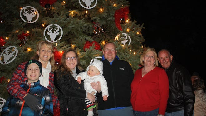 Fort Thomas' annual Christmas tree, courtesy of the Donnelly family, was lit Dec. 6 during the city's annual Holiday Walk. From left are Kolton Smith, 9, and his mother Kathy Donnelly Smith, Laura Mauhart and her 13-month-old daughter Lucy, Steven Maushart and Nancy Donnelly Maushart and her husband, Don Maushart. Don planted the pine tree in 1983 at a home, still owned by the family, at West Villa Place.