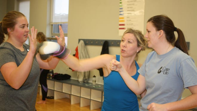 Kate Zembrodt, Campbell County YMCA board chairwoman and kickboxing instructor, shows Jessica Berberich of Independence how to punch with her sparring partner Nancy Morrison of Florence.