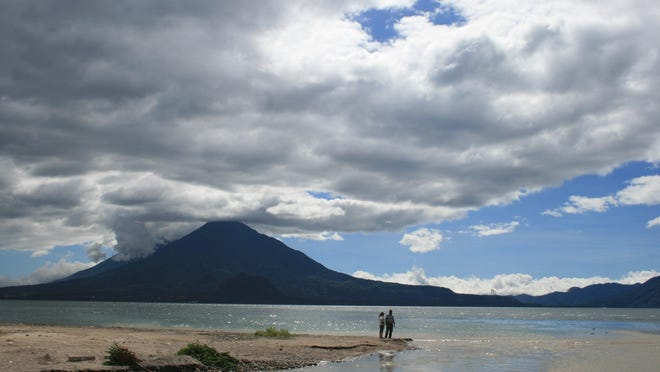 A volcano sits in the distance at Lake Atitlan in Guatemala's Western Highlands. The area is tourist-friendly and rich in the Mayan culture.