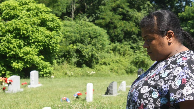 A file photo taken prior to the vandalism showing Krista Dilworth of Walton visiting the Mary E. Smith Cemetery.