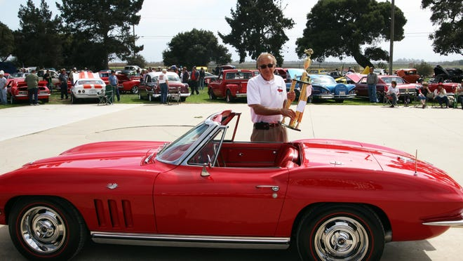 Ray Espinosa holds his Best of Show trophy as he stands behind his Corvette Convertible