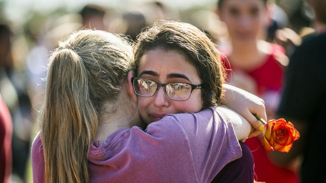 Juniors Staci Esterman (right) and Jaclyn Corin hug after a vigil at Pine Trails Park in Parkland, Florida, on Thursday, Feb. 15, 2018 after a shooting at Marjory Stoneman Douglas High School in Parkland on Feb. 14 took 17 lives.