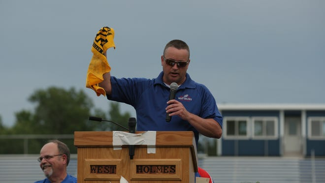 Coach Bill Ashcraft breaks out his Terrible Towel to keep him from crying during a tribute to his former teammate and friend Aaron Kaufman Sunday at West Holmes Knights Stadium.