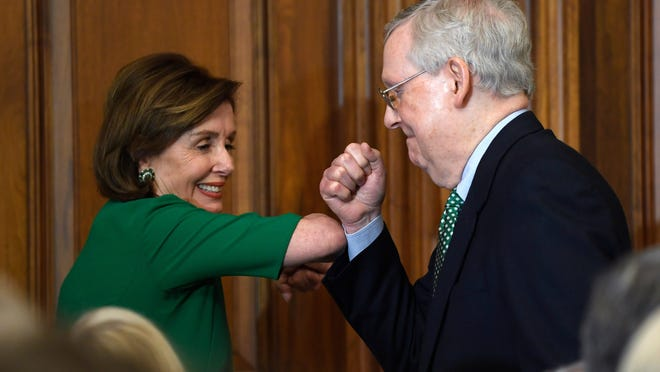 House Speaker Nancy Pelosi and Sen. Majority Leader Mitch McConnell bump elbows as they attend a lunch with Irish Prime Minister Leo Varadkar on Capitol Hill on March 12, 2020.