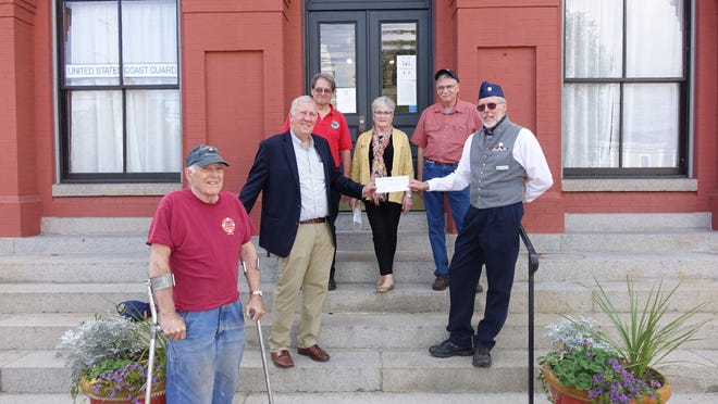"""Doug McQuaid (r., with sunglasses, cap), a former crewman on the USCGC Southwind, presents a check from the former Southwind Association to Capt. Greg Ketchen, president of the Coast Guard Heritage Museum. Foreground: Jim Ellis, blacksmith at the museum;  back row: """"Buck"""" Baley, museum vice president; Pat Garrity; and Bill Collette."""