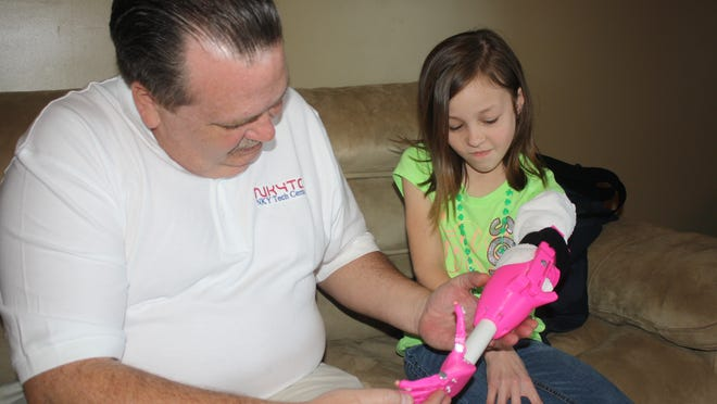 John Richardson helps Emma Ranshaw learn how to use her new arm and hand he built for her using his 3-D printer.