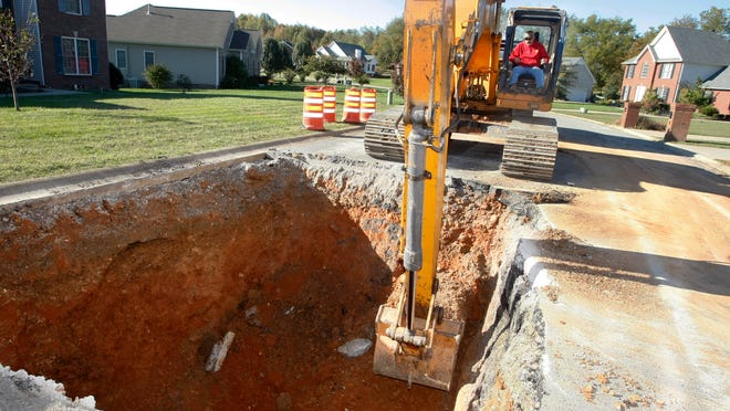 Montgomery County Highway Department worker Reggie Norfleet removes dirt from a large sinkhole Wednesday on Rabbit Run Trail, near Drake Road.