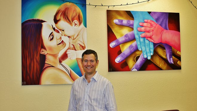 """John """"Doc"""" Edwards stands in his chiropractic office where he treats infants, pregnant women and their families. The art on the wall consists of paintings by his wife, Erica Edwards."""